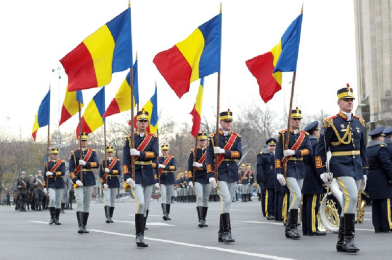 Mai mulți soldați defilează cu tricolorul în mână