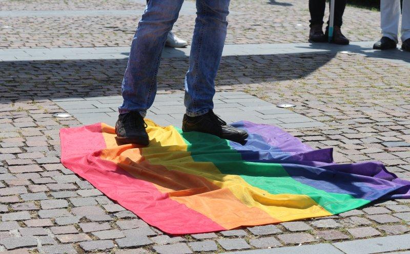 Simpatizanții Noua Dreaptă, stând pe un steag LGBT la mitingul din Cluj-Napoca *foto: Ziua de Cluj