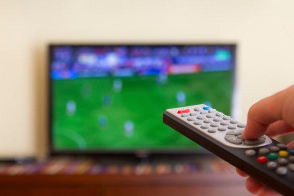 Barbat urmarind un meci de fotbal la tv